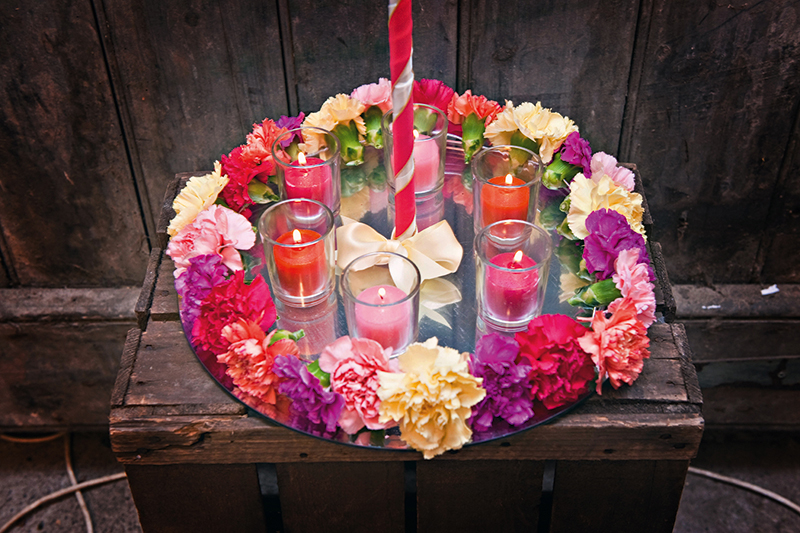 This brilliantly effective centrepiece makes use of a mirror and candles rather than lots of expensive stemmed flowers Photo: borders-photographer.co.uk