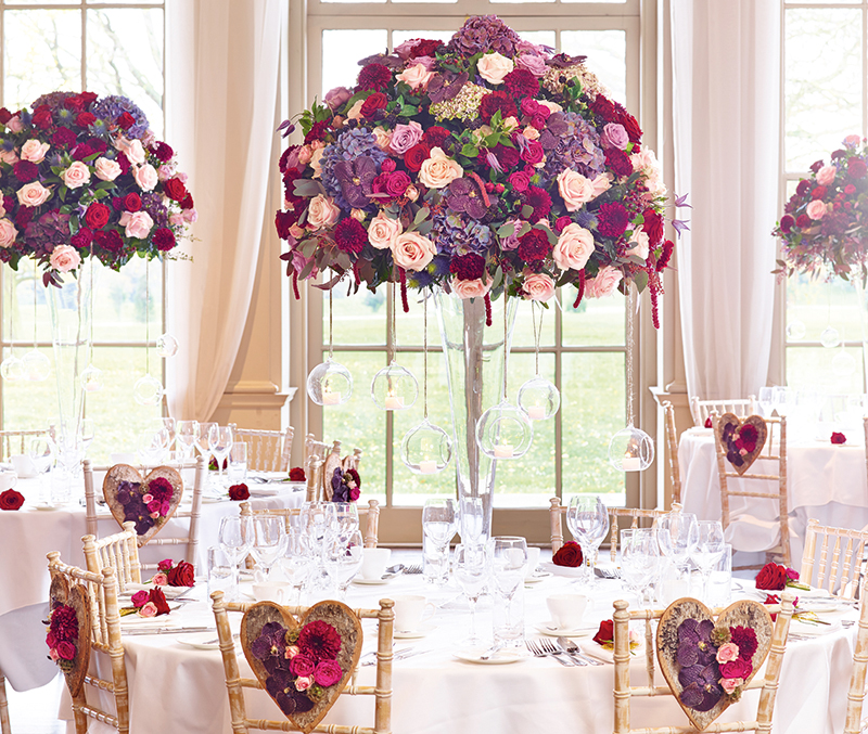 The all-white background really helps these colourful centrepieces stand out in this room set-up by Interflora