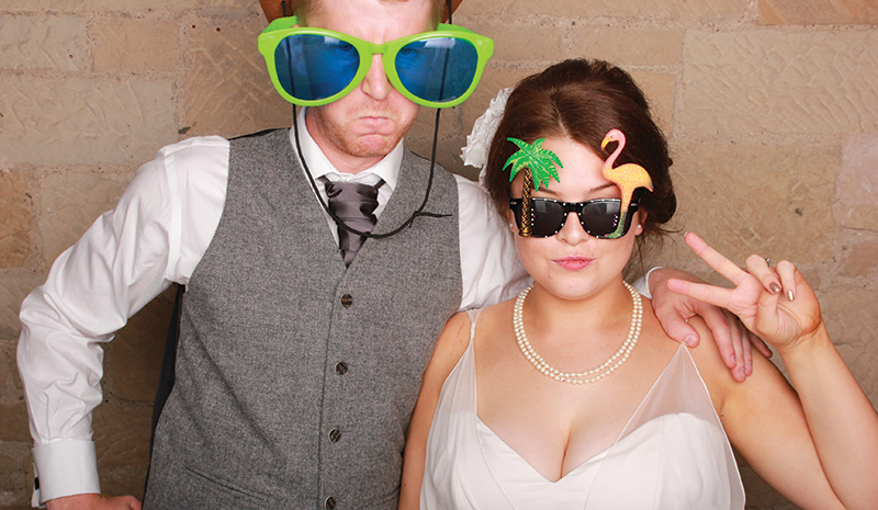 The bride and groom are ready for their close-up with funny specs in an Odd Box Photobooth