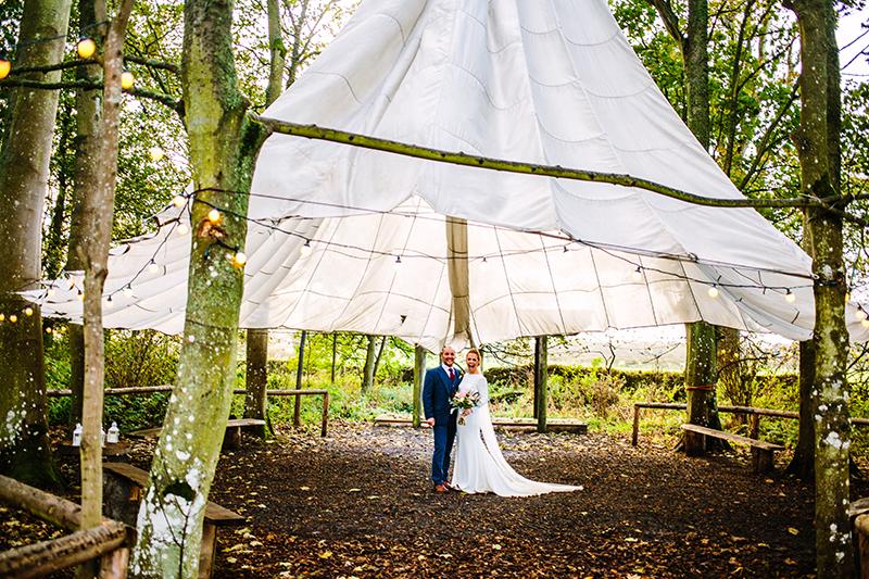 bride and groom under teepee