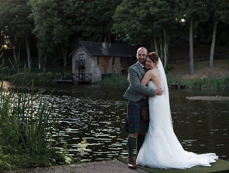 bride and groom in front of pond