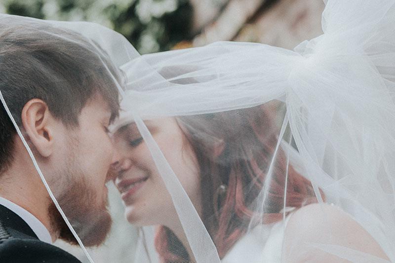 couple kissing under veil