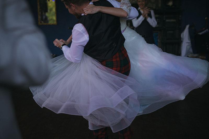 groom in tartan trousers swinging bride on the dancefloor