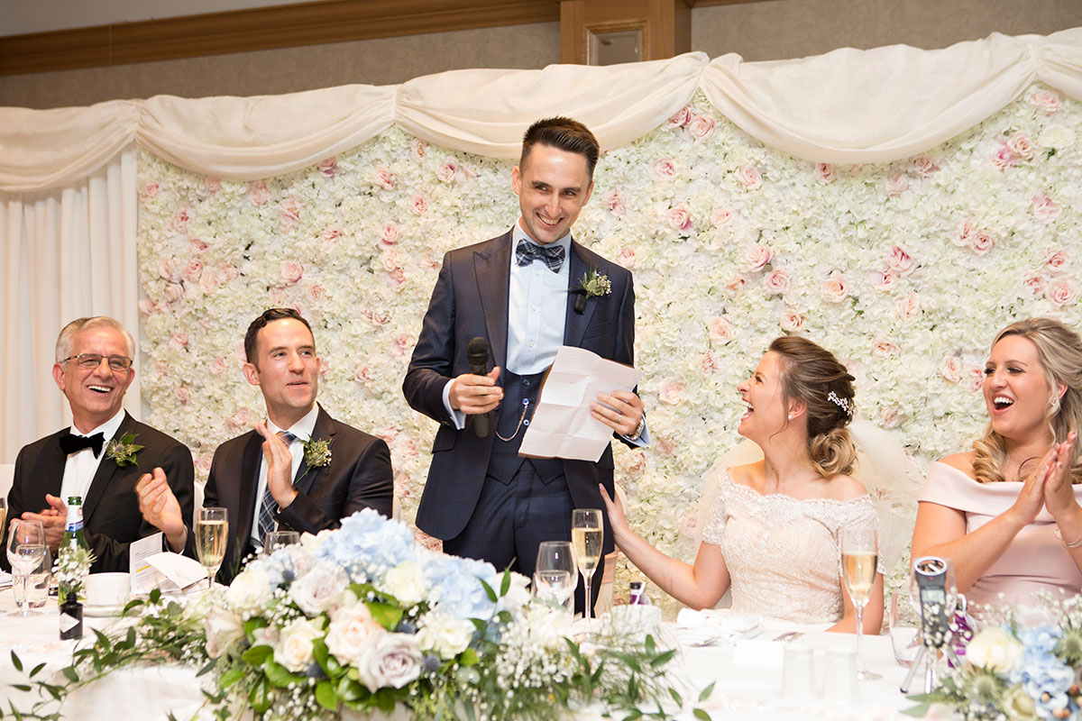 groom-giving-a-speech-in-front-of-floral-wall