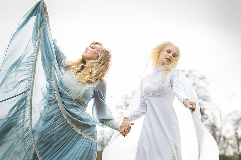 two boho brides dancing in a field