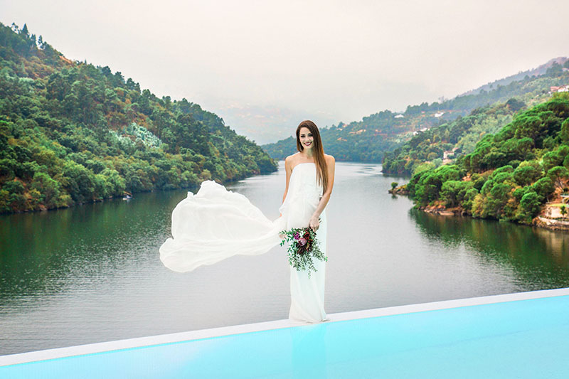bride posing against river backdrop in Porto