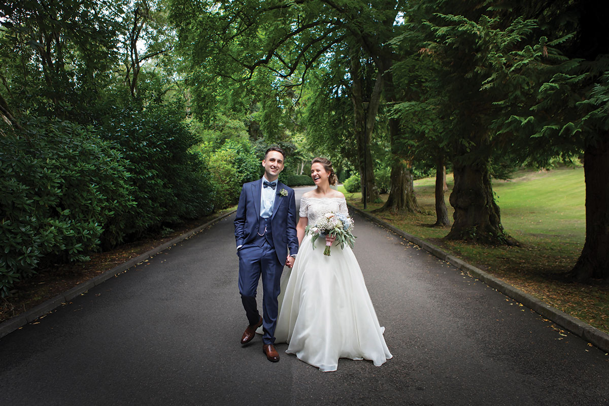 bride-in-lace-wedding-dress-and-groom-wearing-blue-suit