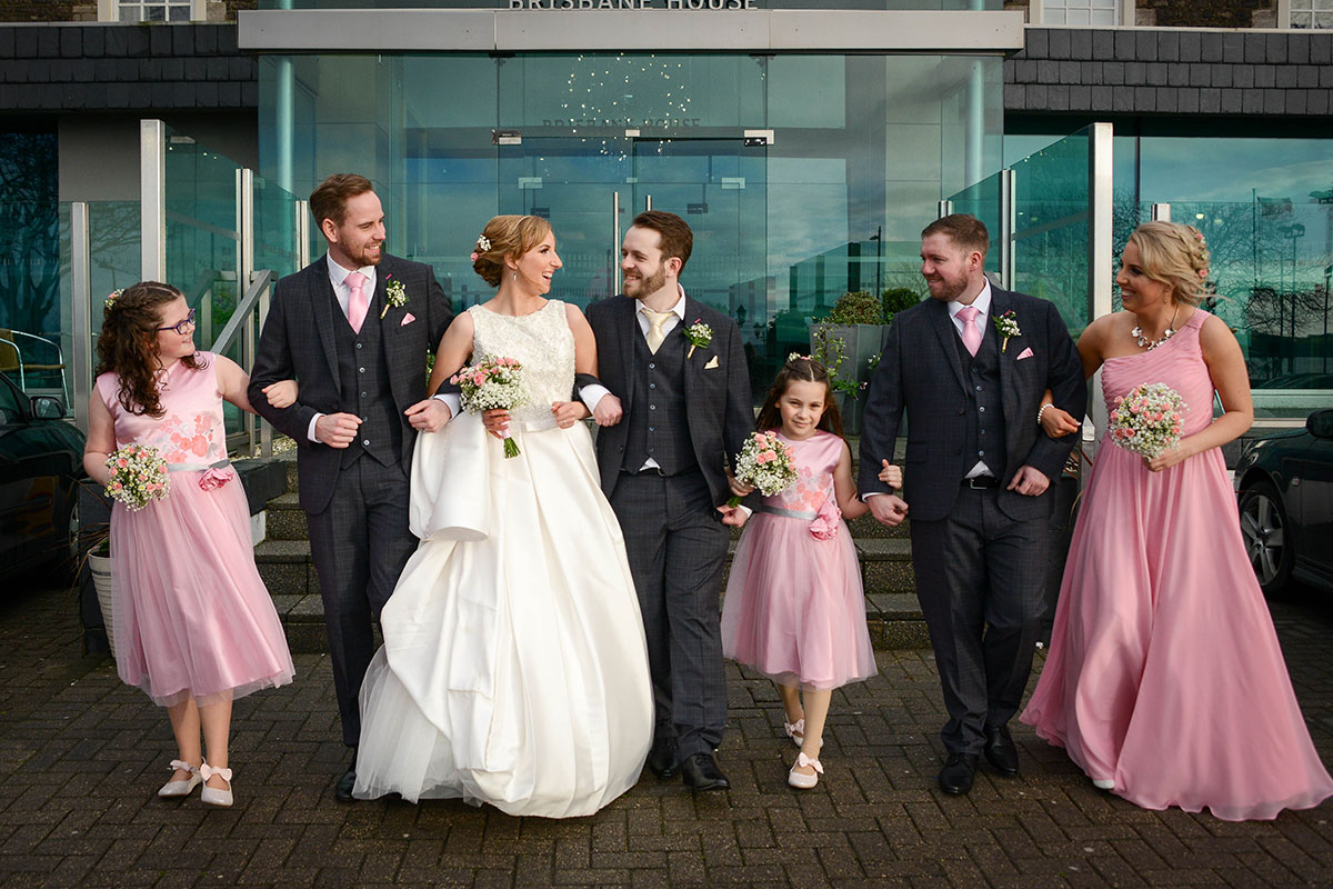 bridal-party-in-pink-bridesmaid-dresses-and-blue-suits
