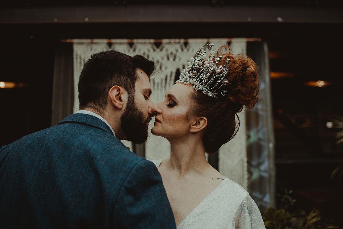 bride-wearing-tall-tiara-kissing-groom-in-blue-suit