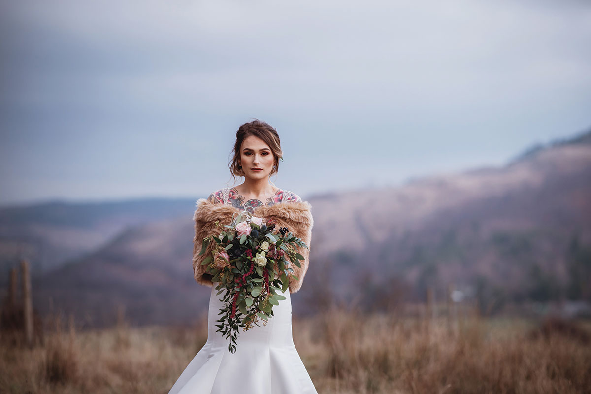 bride-with-tattoos-and-fur-wrap-and-rustic-wedding-flowers