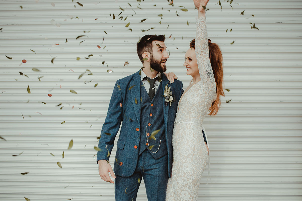 bride-in-jumpsuit-throwing-confetti-with-groom