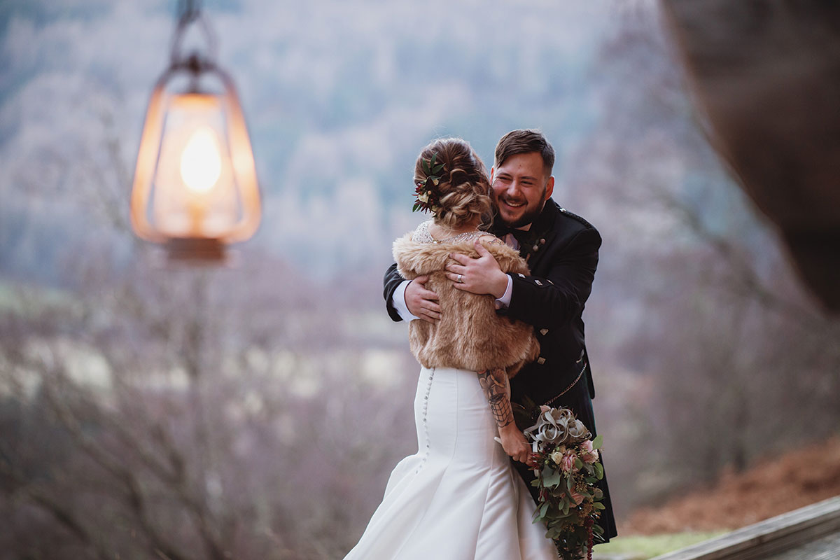 bride-and-groom-embracing-on-balcony-of-eagle-brae