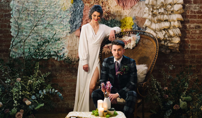 bride-and-groom-on-rattan-chair-in-front-of-frill-factory-backdrop