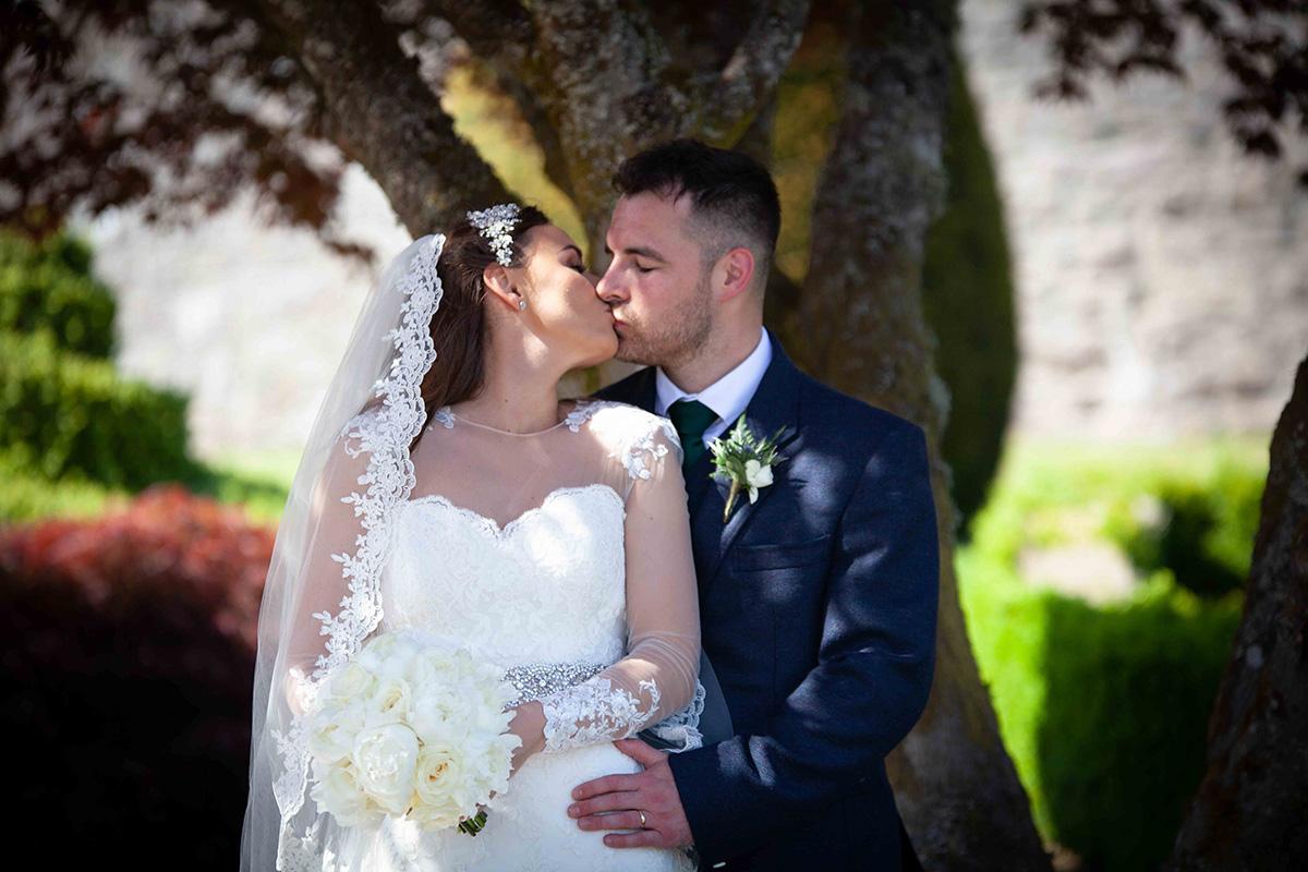 bride-in-long-lace-veil-kissing-groom-in-kilt