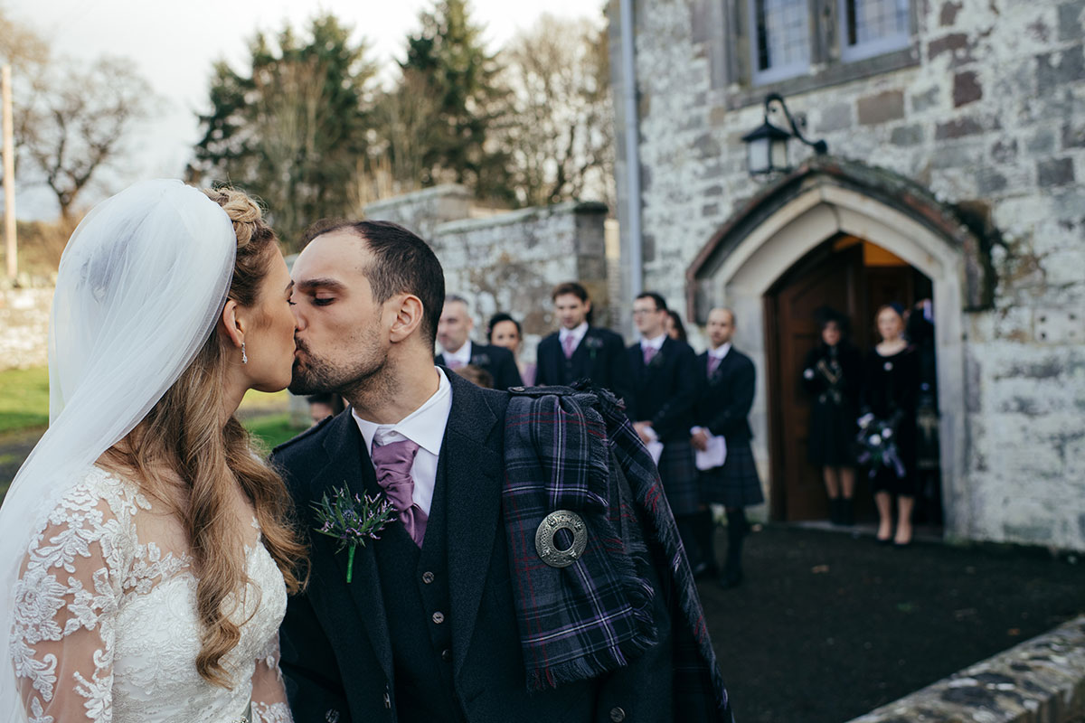 bride-and-groom-kissing-outside-church