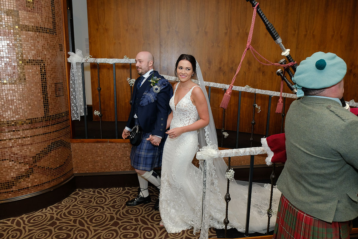 bride-and-groom-being-piped-into-reception-room