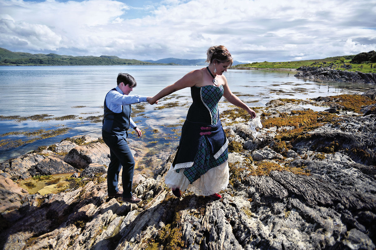 brides-walking-across-rocks-on-shore
