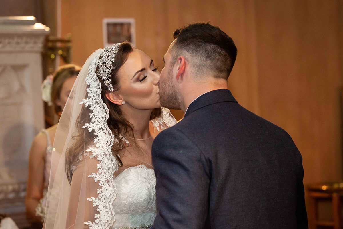 bride-in-lace-veil-kissing-groom-during-ceremony