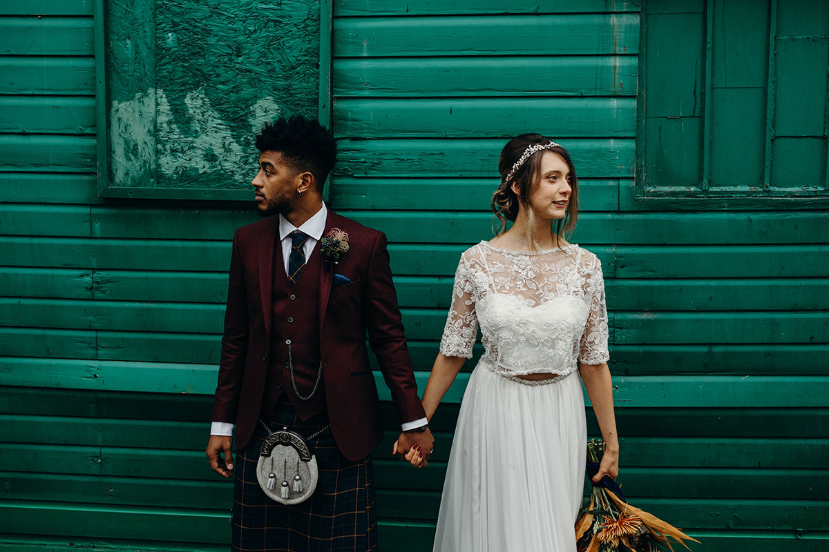 bride-and-groom-in-front-of-green-wood-wall