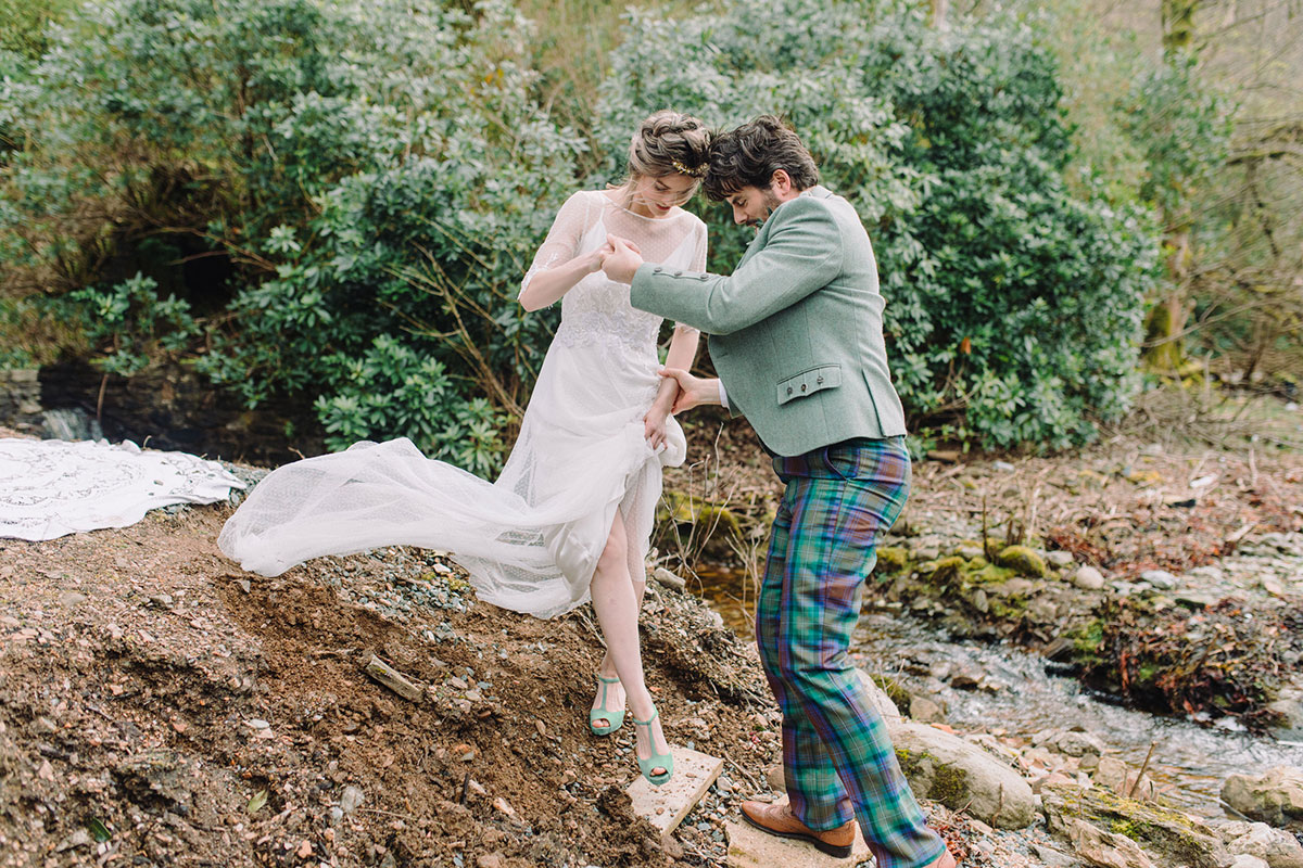 groom-helping-bride-climb-down-embankment