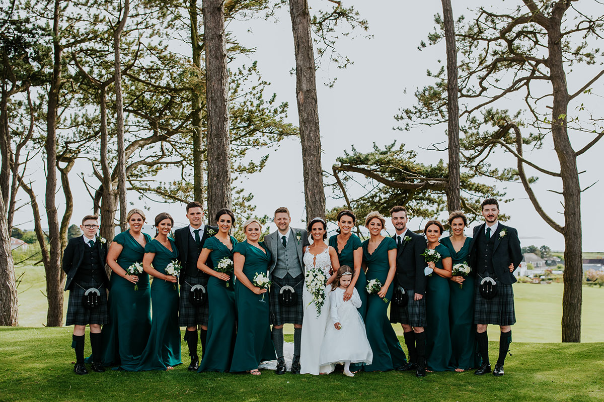 bridal-party-with-bridesmaids-in-green-dresses-and-groomsmen-in-kilts