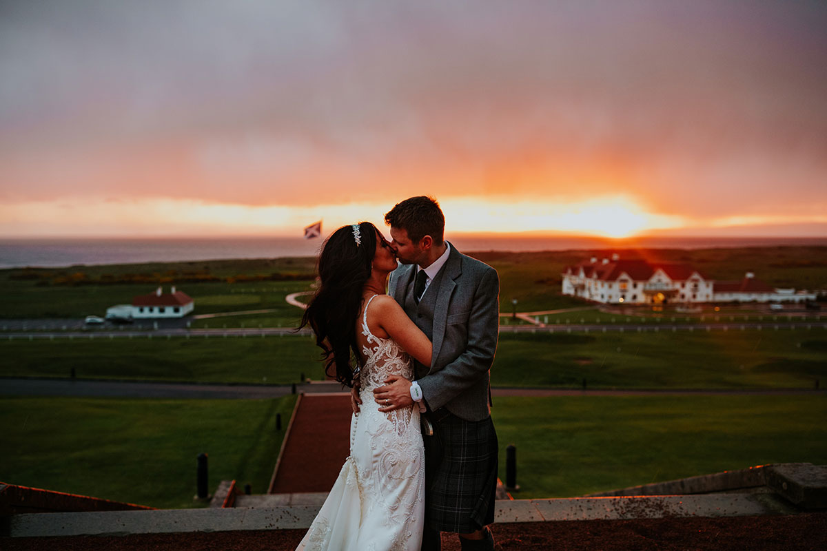 bride-and-groom-kissing-at-sunset-outside-turnberry