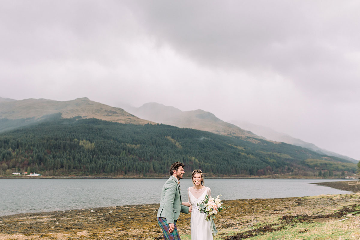 bride-and-groom-in-tweed-kilt-outfit-laughing-by-loch
