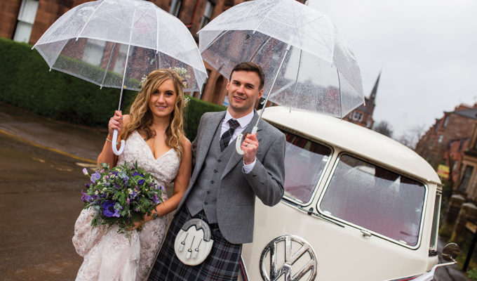 bride-and-groom-posing-under-umbrellas-in-the-rain