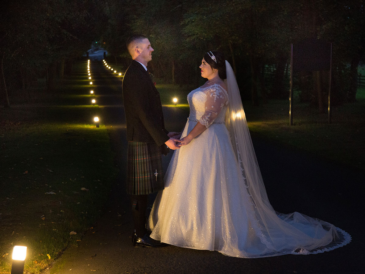 bride-and-groom-holding-hands-outside-at-night