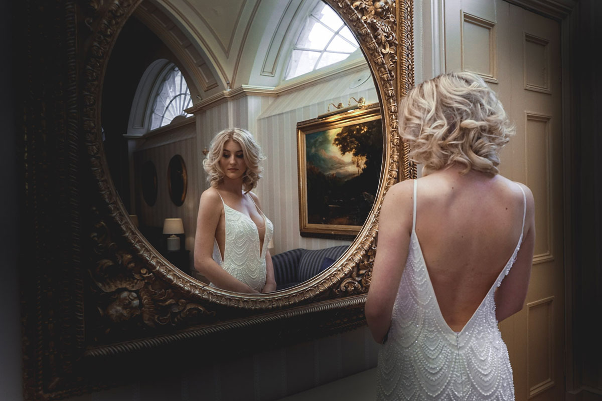 blond-bride-looking-in-ornate-mirror