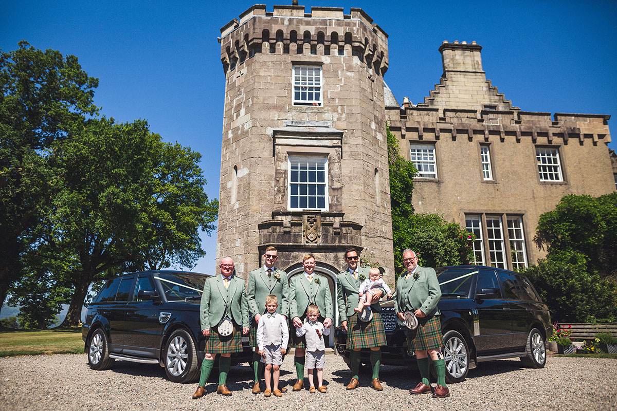 groom-and-groomsmen-in-front-of-range-rovers