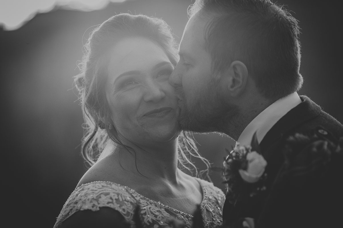 black-and-white-photo-of-groom-kissing-bride-on-the-cheek