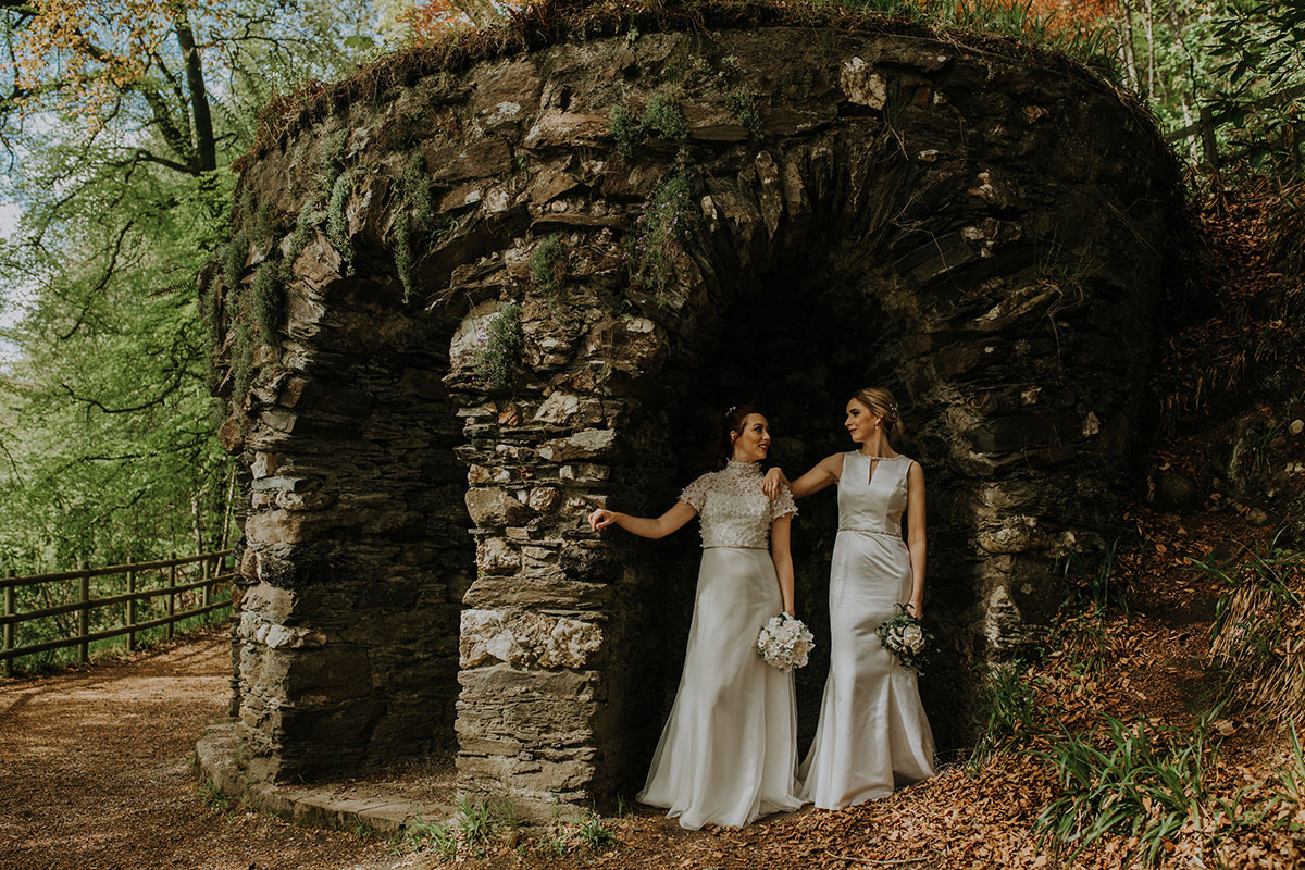 two-brides-under-stone-arch