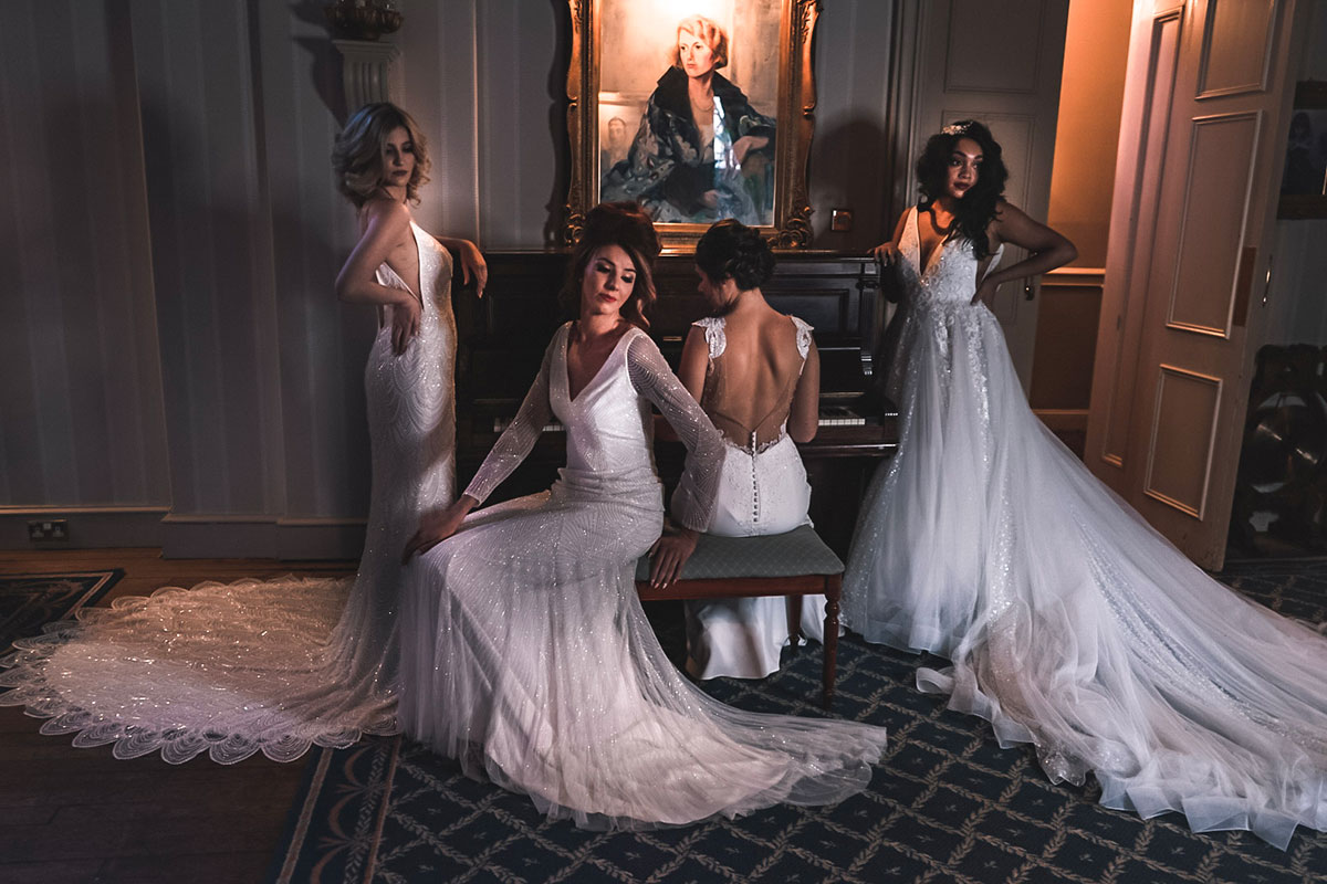 four-bridal-models-wearing-wedding-dresses-posing-at-piano