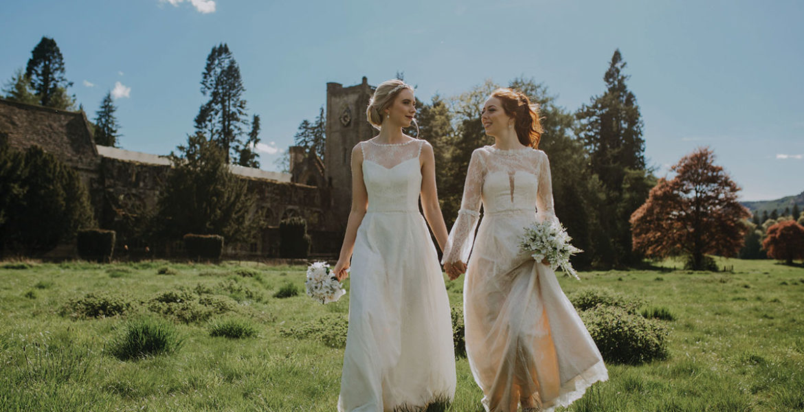 two-brides-holding-hands-and-walking-through-field
