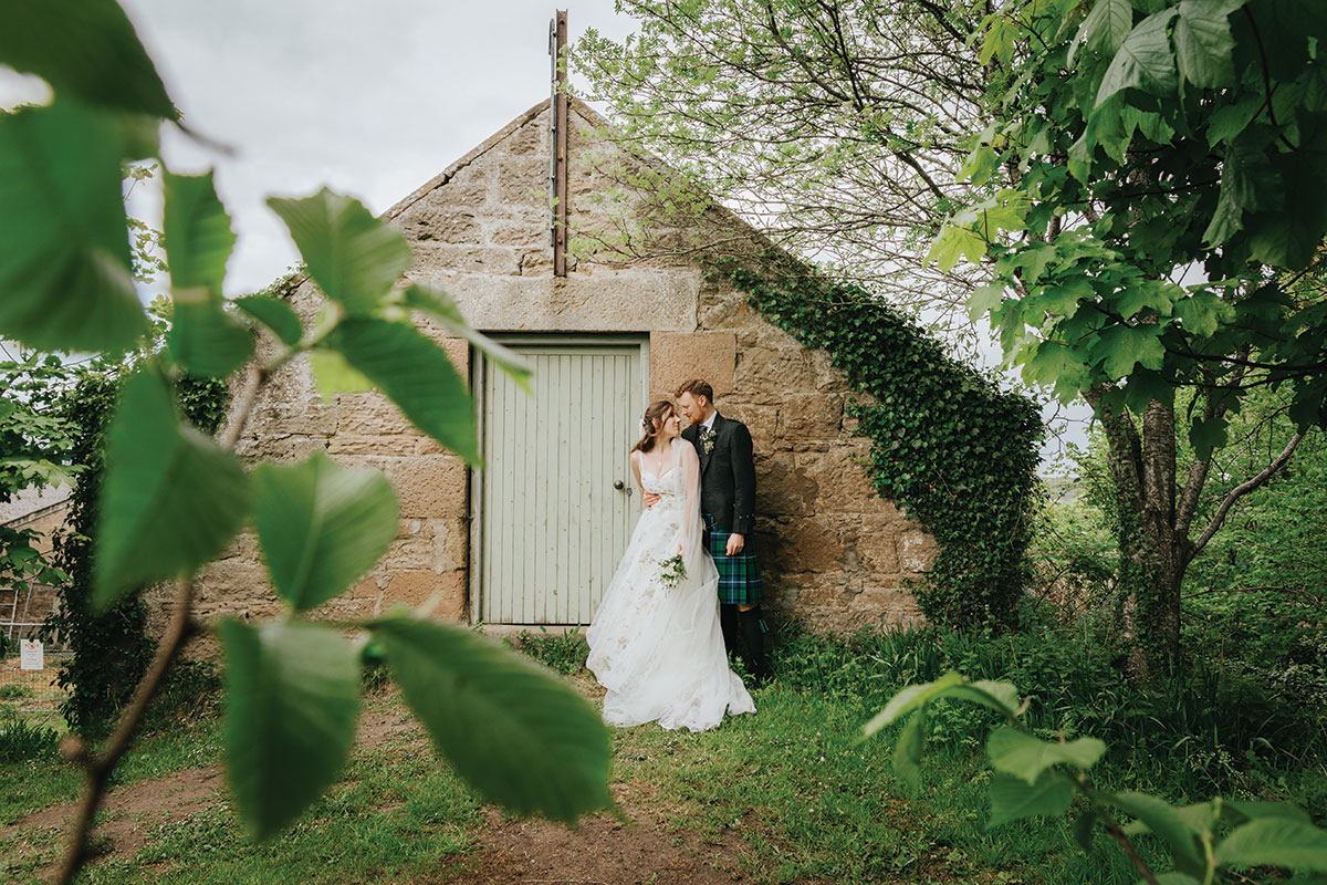 bride-and-groom-outside-small-stone-outhouse