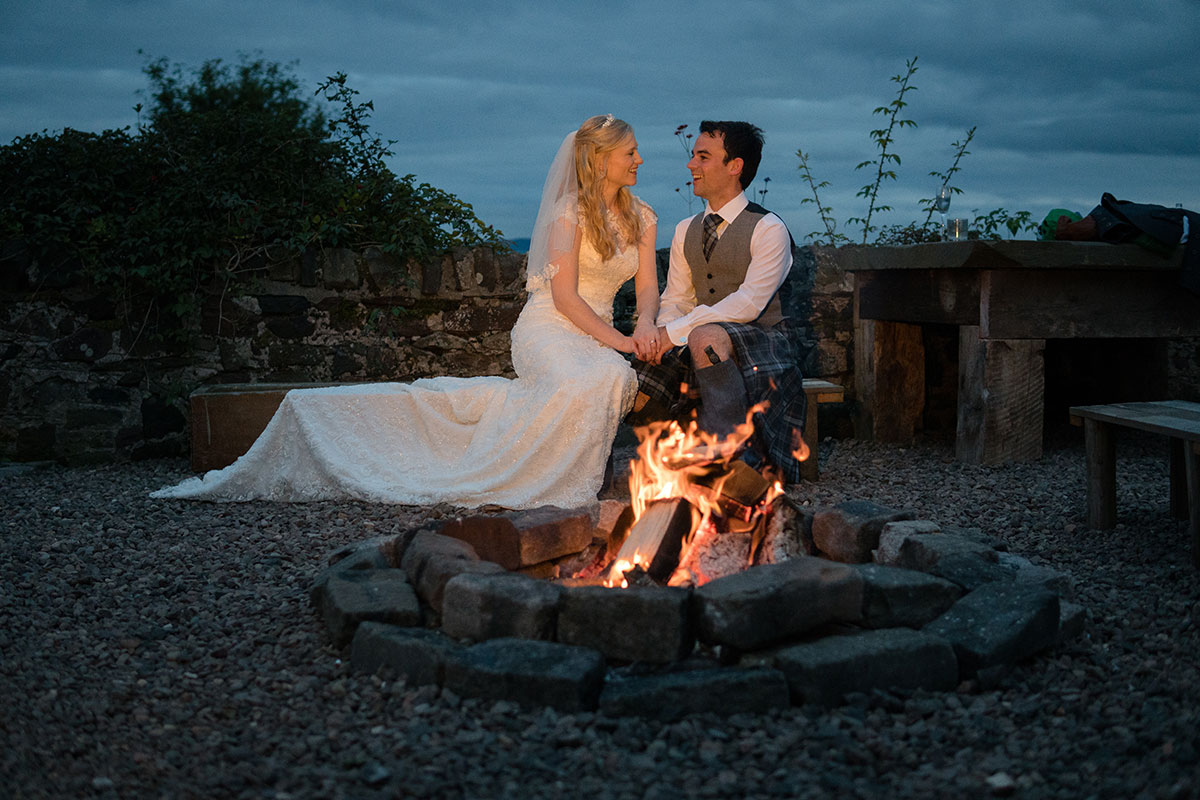bride-and-groom-sitting-by-fire-outside
