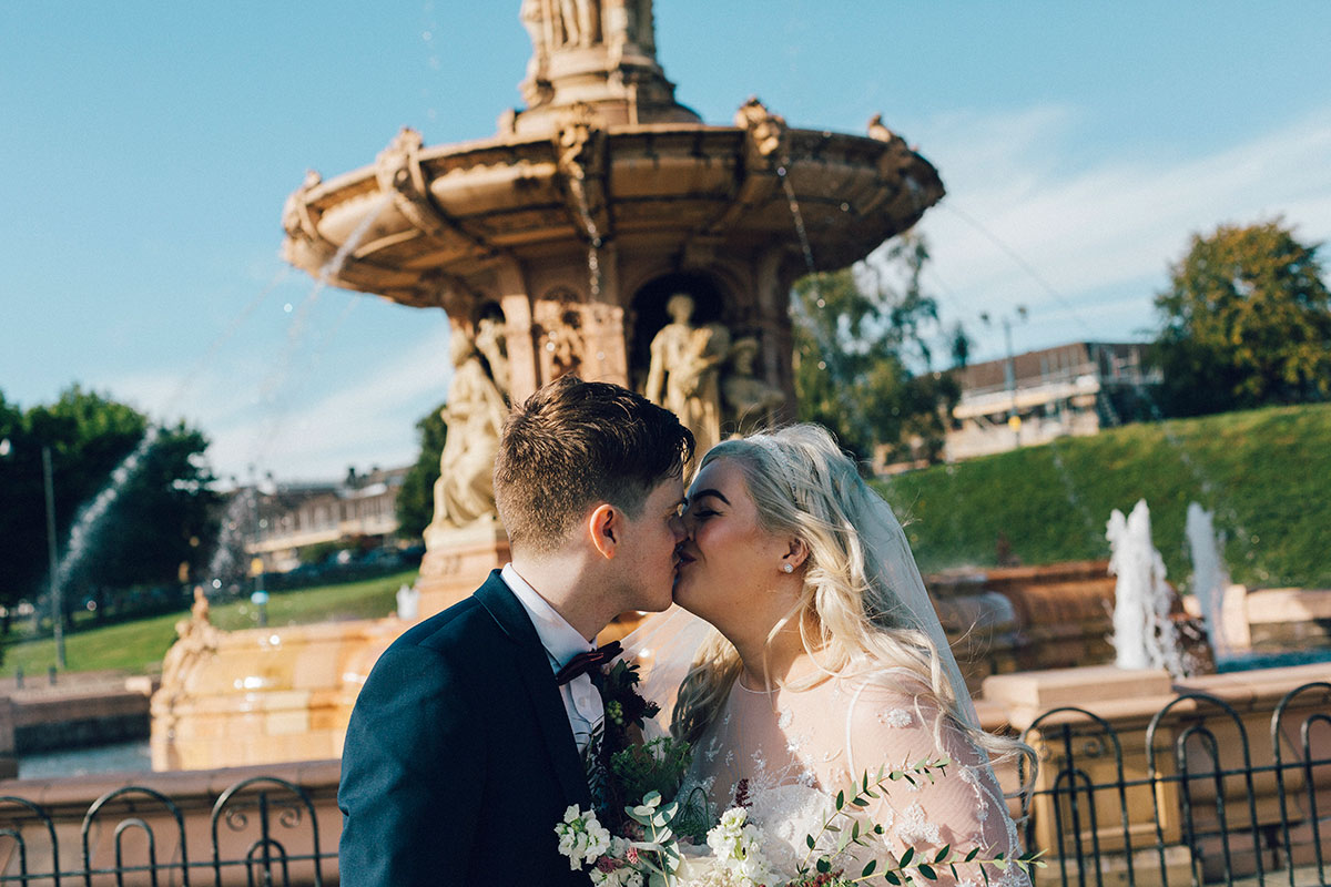 bride-and-groom-kissing-next-to-fountain-in-glasgow-green