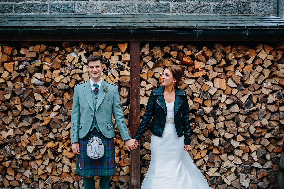 bride-and-groom-holding-hands-in-front-of-log-display-in-castle-grounds