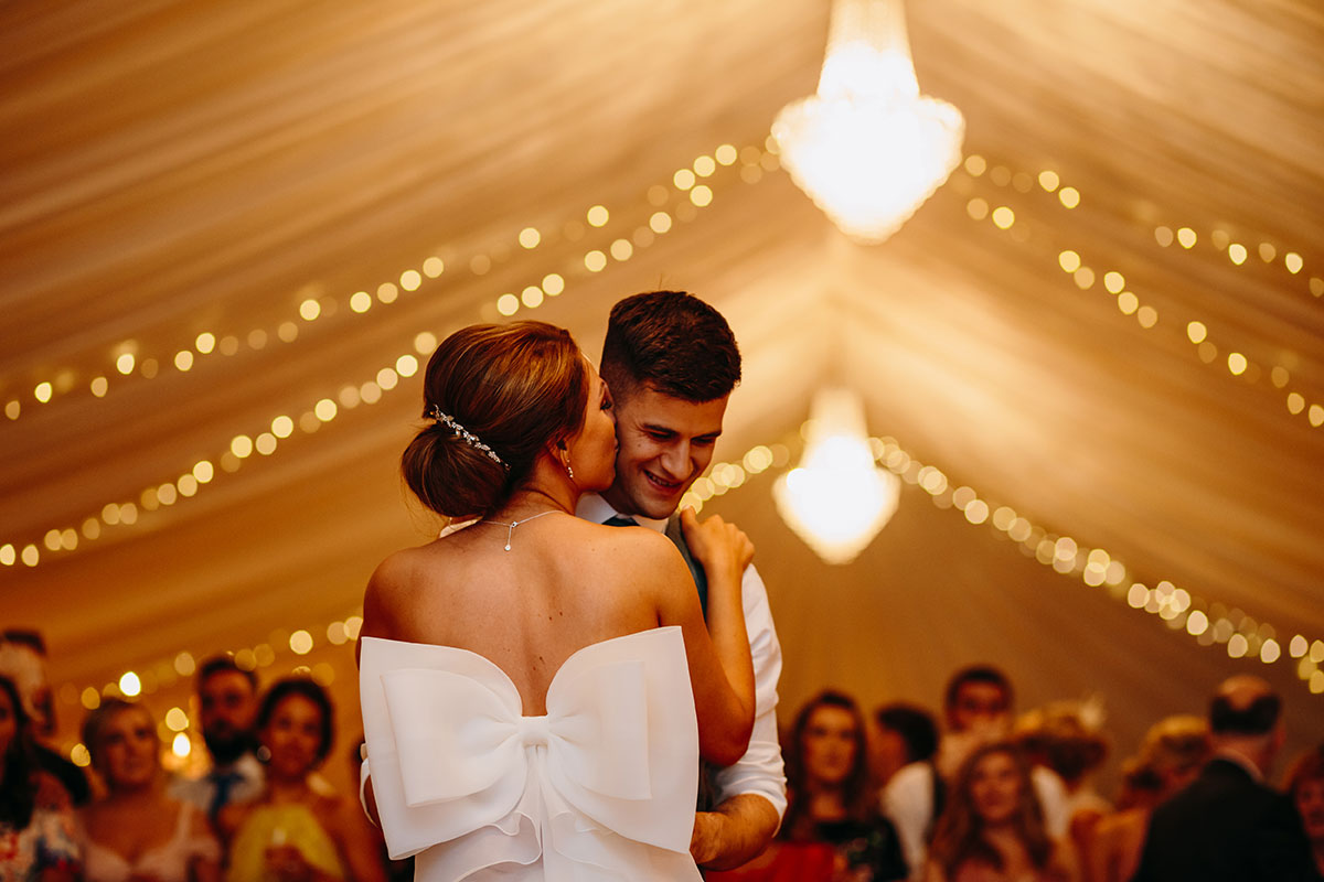 bride-kissing-grooms-cheek-during-first-dance