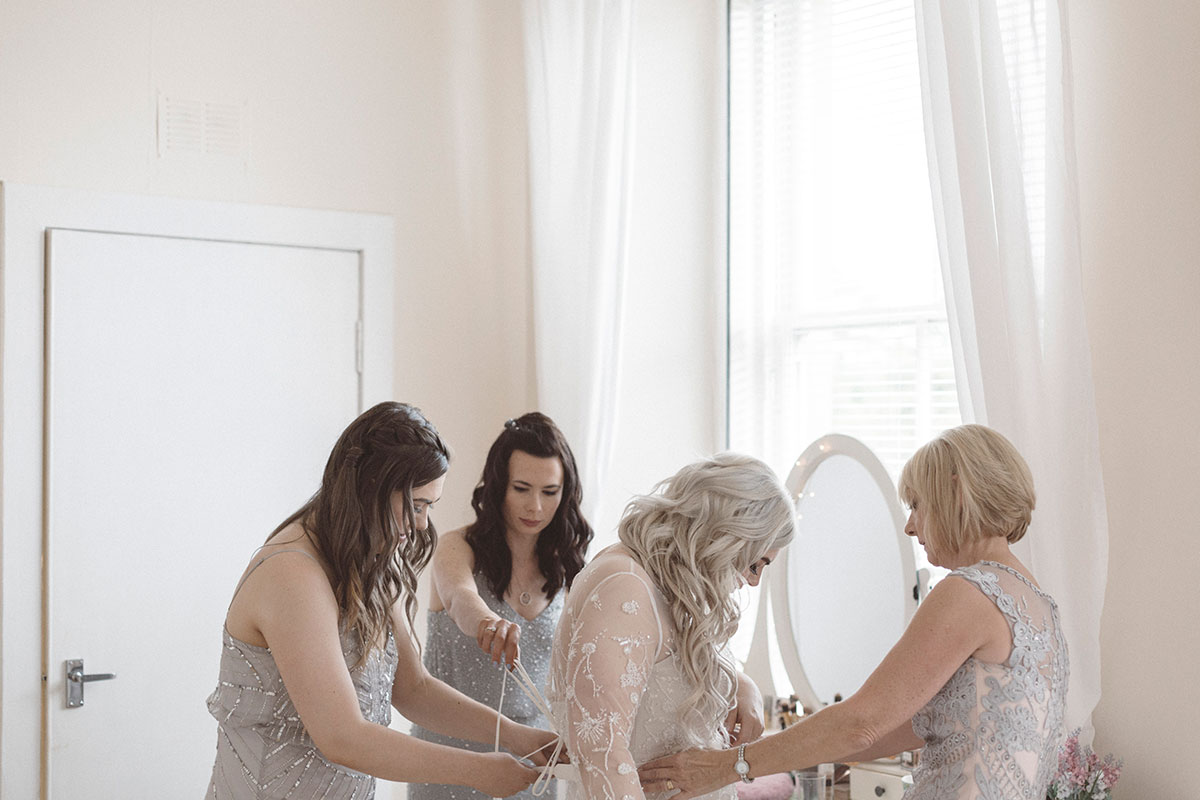 bridesmaids-helping-lace-brides-dress-up