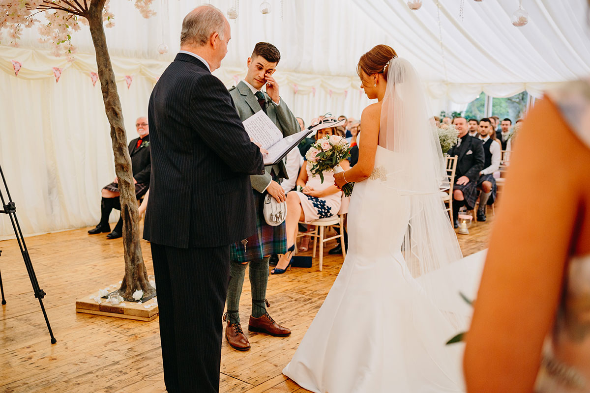 groom-in-kilt-outfit-wiping-eyes-during-ceremony