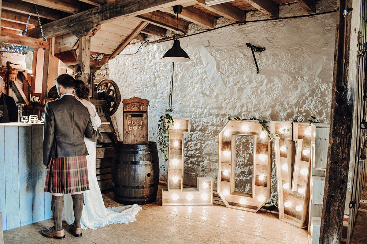 couple-at-barn-bar-with-light-up-letters