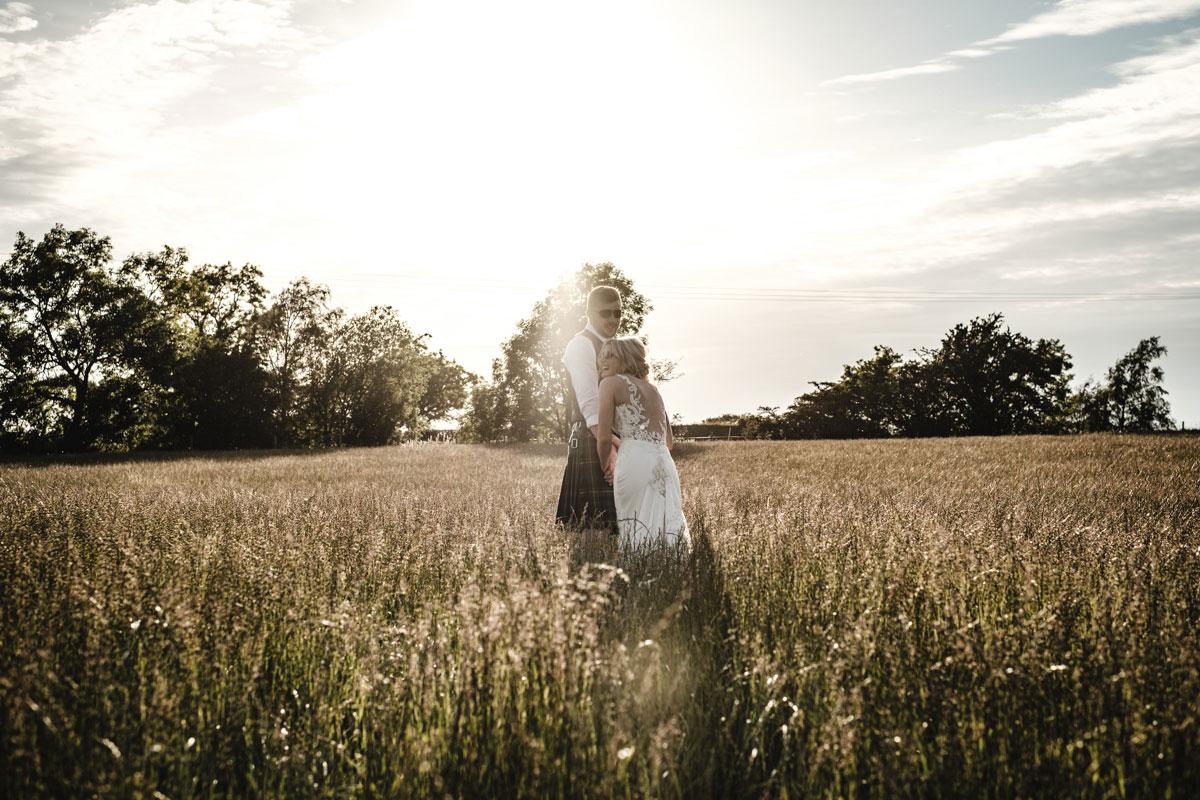 bride-and-groom-wearing-sunglasses-in-field