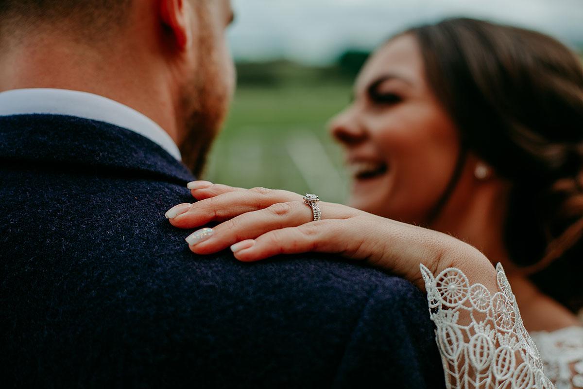 close-up-of-brides-ring-on-grooms-shoulder