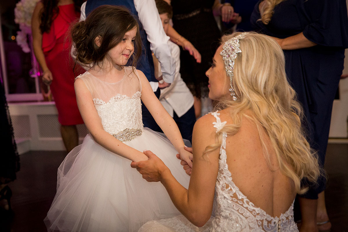 bride-talking-to-flower-girl-in-white-dress-with-silver-gems