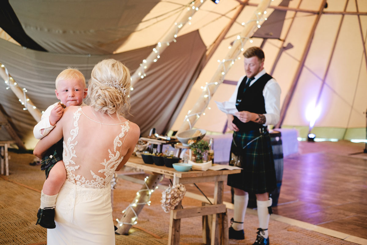 groom-giving-speech-whilst-bride-holds-their-son