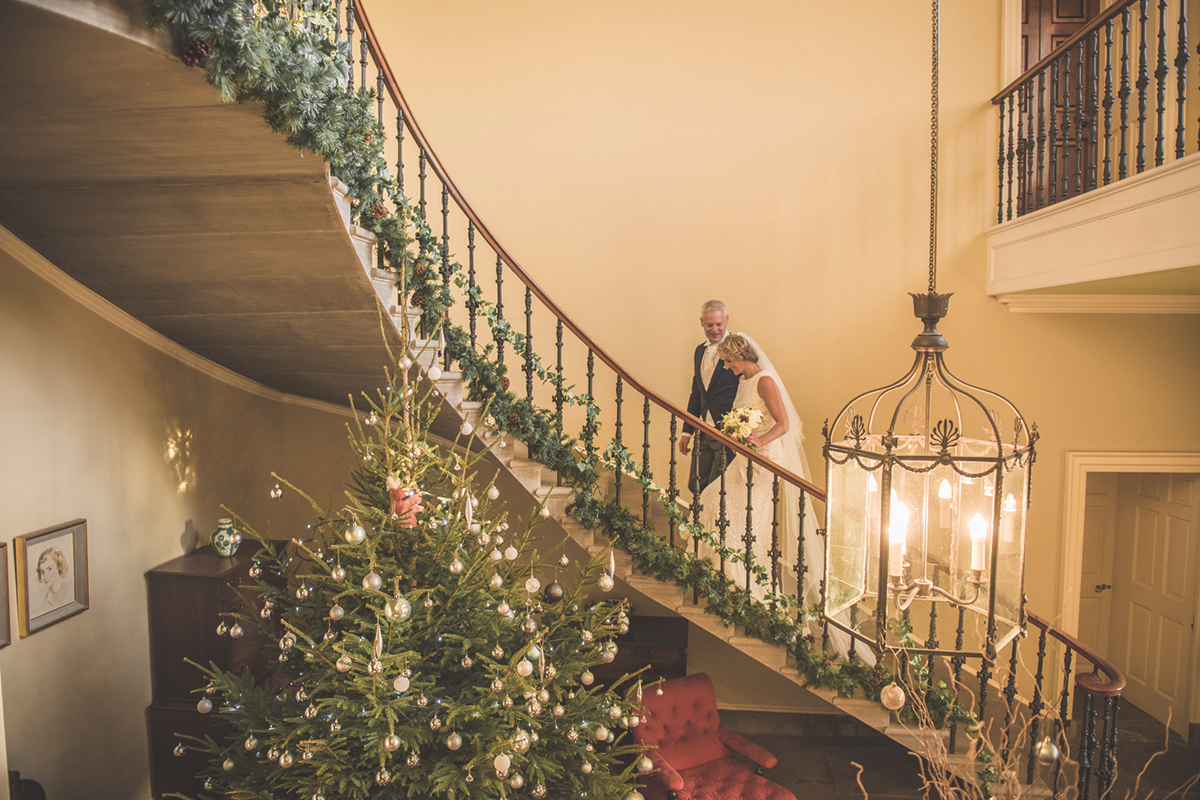 Wedderburn-couple-walking-up-stairs-decorated-for-christmas