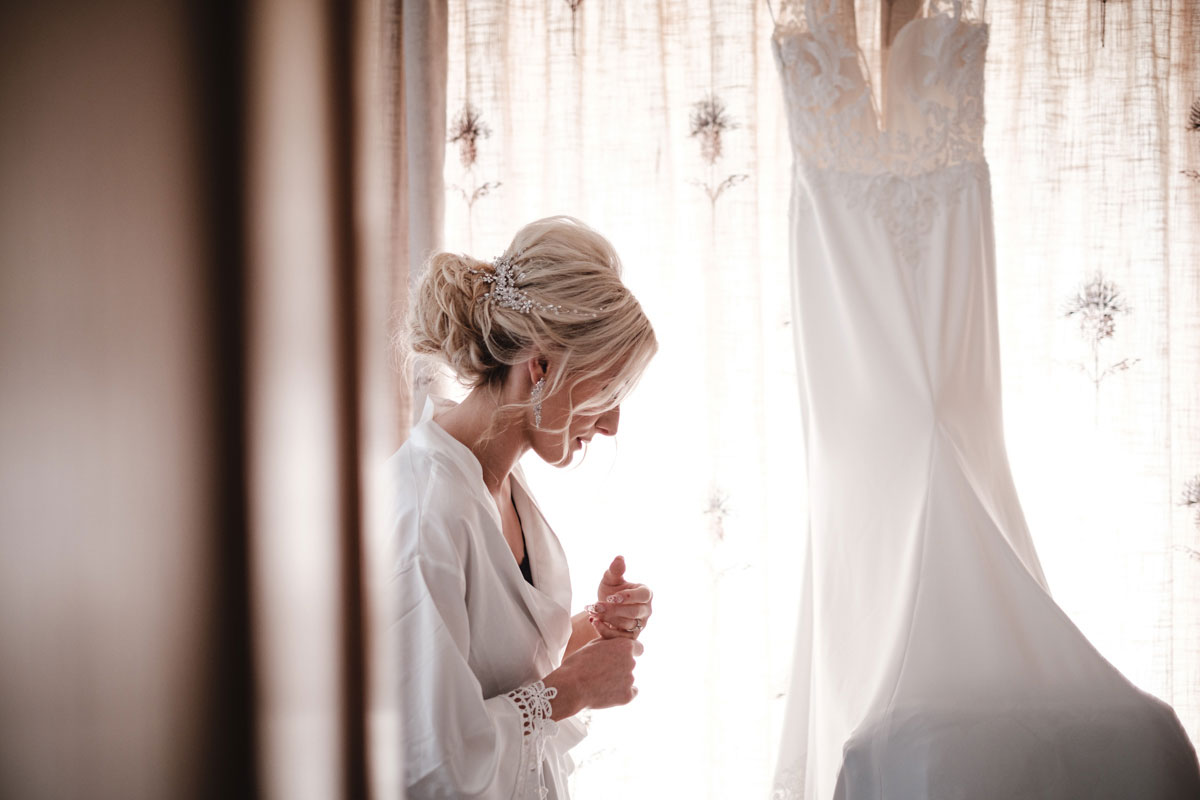 bride-standing-in-robe-with-wedding-dress-hanging-up