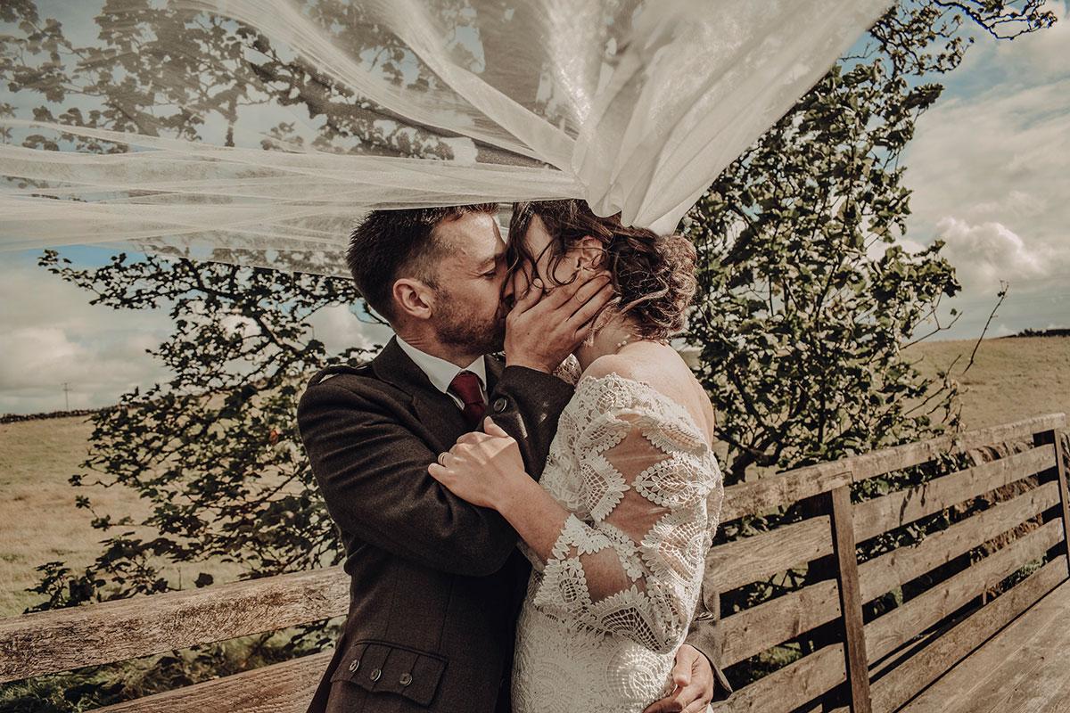 bride-and-groom-kissing-under-veil